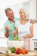 Senior Couple Preparing Salad In Modern Kitchen
