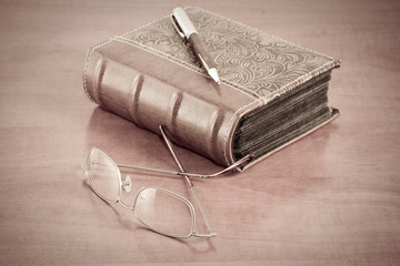 old book with reading glasses and pen