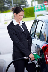 business woman filling car at gas station