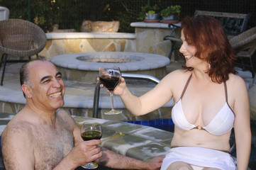 couple enjoying wine by the pool