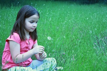 One young girl about to blow on dandelion