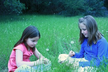 Two young girls about to blow on dandelions