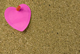 Pink heart shaped note on with red thumb tack on bulletin board poster
