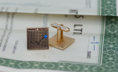 Cuff links & stock market report on stock certificate share