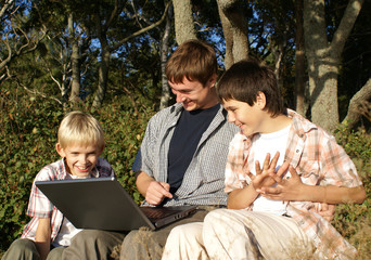 Father and sons sitting in the park using a laptop