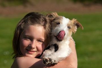 Kind hält einen Hund auf dem Arm