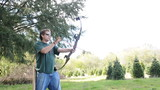 Man Casually Practicing Archery with Bow and Arrow Outside