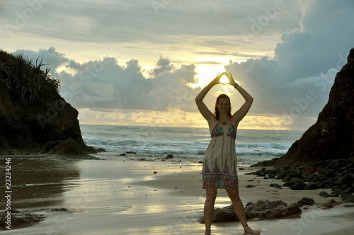 Woman holds the sun in her hands on the beach