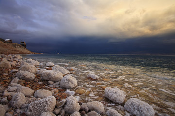 The spring thunder-storm. The coastal stones covered by salty ad