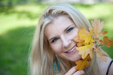 young pretty autumn woman outdoors smiling  with yellow leafs