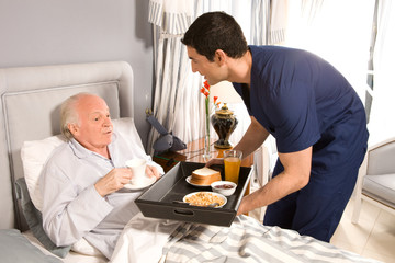 Offering breakfast to old senior man