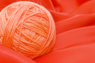 Ball of threads on a red fabric