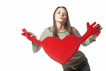 Girl with red heart-shape cushion in hands kiss you