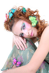Red-haired woman with flowers and butterflies on her head sittin