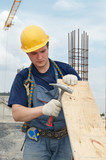 builder working with hammer and plywood poster