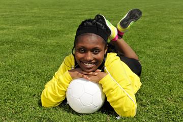 Fussballspielerin mit Fussball auf Fussballplatz