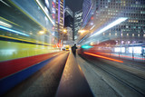 Fast moving bus lights blurred over modern city background