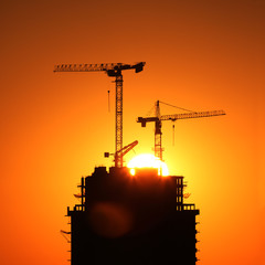Construction cranes in building at sunrise