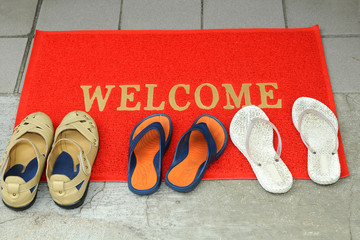 Welcome Mat At The Doorstep With Pairs Of Footwears