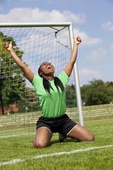 jubelnde Fussballspielerin zeigt beide Daumen hoch