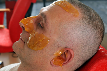 Epilation wax applied to an adult man's face.