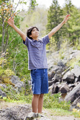 Teenage boy raising hands in praise