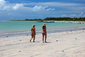 Girls walking on the green sea beach in Alagoas, Brazil