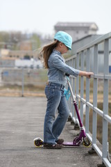 girl with scooter standng at fence