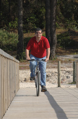 Fat man cycling on the seaside