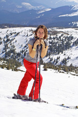 Girl with skis staying on a mountain slope