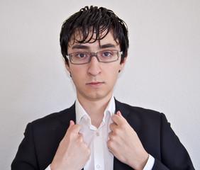 Jeune cadre avec les mains sur le col de sa chemise blanche