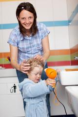 mutter hilft kind beim föhnen