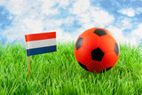 Orange ball and Dutch flag on soccer field