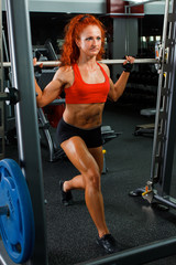 Woman to do exercises at the gym apparatus