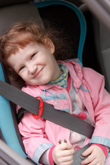 Cute little girl in a baby car seat. Happy Travel