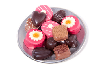 a small plate with delicious chocolats and marzipan isolated ove
