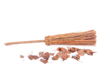 a wooden broom with dried brown leaves
