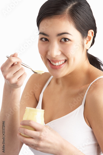 Young Woman Eating Yoghurt In Studio