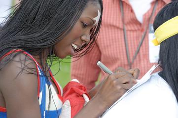 hübsche, dunkelhäutige Sportlerin gibt ein Autogramm