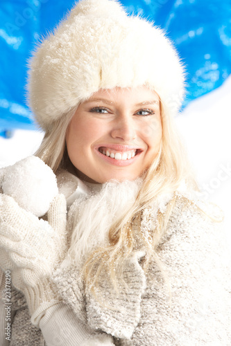 Young Woman Wearing Warm Winter Clothes And Fur Hat Holding Snow