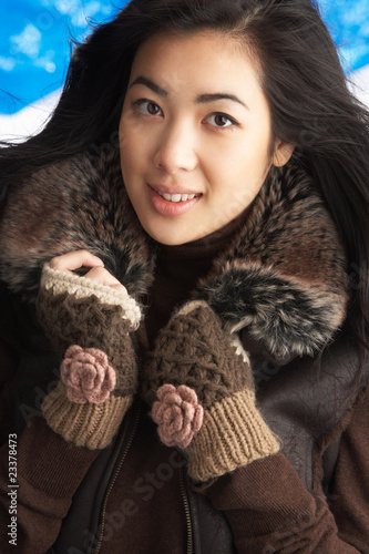 Young Woman Wearing Warm Winter Clothes In Studio