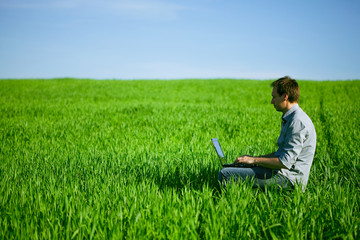 Young man using a laptop outdoors