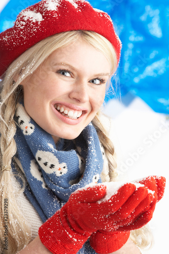 Young Woman Wearing Warm Winter Clothes And Hat Holding Snow In