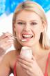 Young Woman Eating Yoghurt In Studio