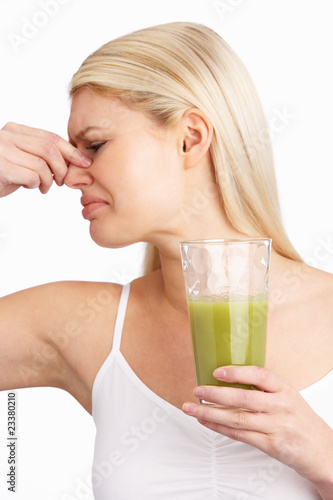 Young Woman Not Enjoying Healthy Drink In Studio