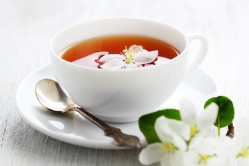 white cup of tea with apple blossoms