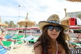 Urlauberin mit Hut am Strand von Mallorca