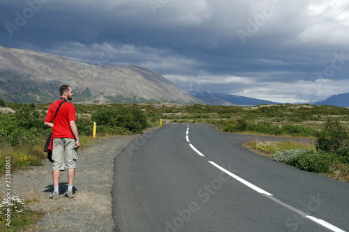 Lonely traveller hitchhiking along the road in Iceland