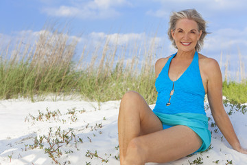 Attractive Senior Woman Sitting In Swimming Costume At Beach