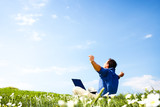 Man working with laptop in a meadow of flowers with copyspace